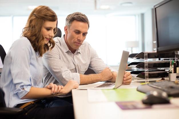 Compañeros de trabajo que trabajan en la computadora portátil en el escritorio