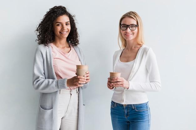 Compañeros de trabajo rubios y étnicos con tazas de café