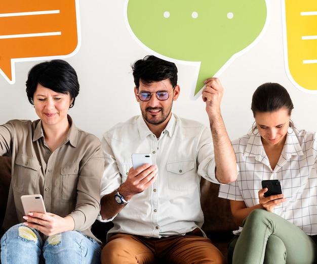 Compañeros de trabajo sentado en el sofá y sosteniendo iconos de mensaje