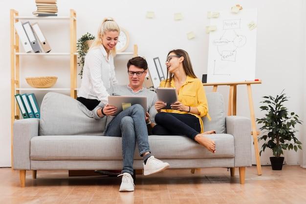 Compañeros de trabajo sentado en el sofá y trabajando en la computadora portátil