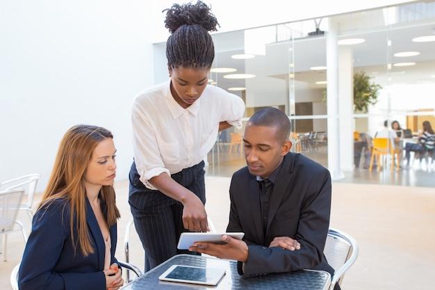 Compañeros de trabajo serios discutiendo informes en un café al aire libre