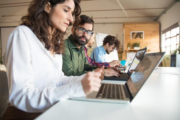Compañeros de trabajo serios con laptops discutiendo proyecto
