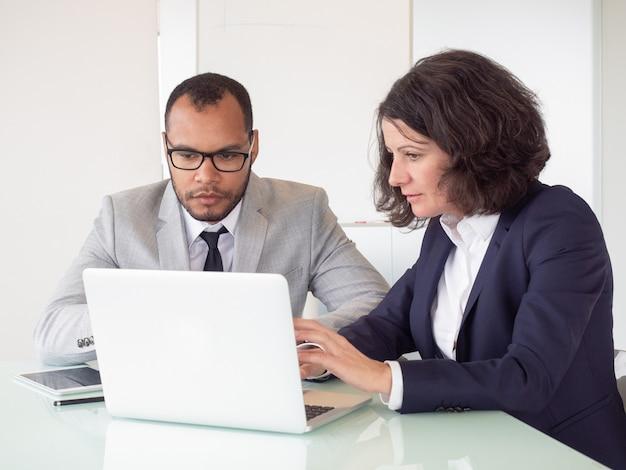 Compañeros de trabajo serios usando laptop