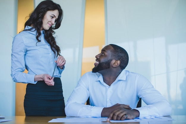 Compañeros de trabajo sonriendo uno al otro