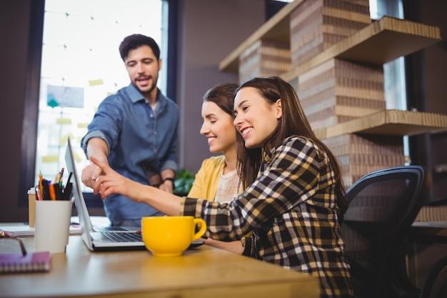 Compañeros de trabajo sonriendo mientras apunta a la computadora portátil en el escritorio