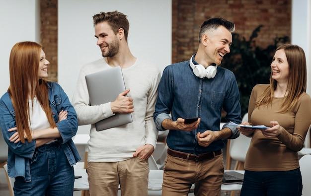 Compañeros de trabajo sonrientes hablando en la oficina
