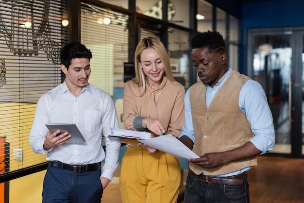 Compañeros de trabajo sonrientes mirando documentos juntos