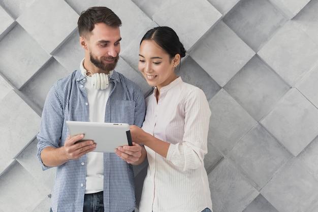 Compañeros de trabajo sonrientes mirando tableta