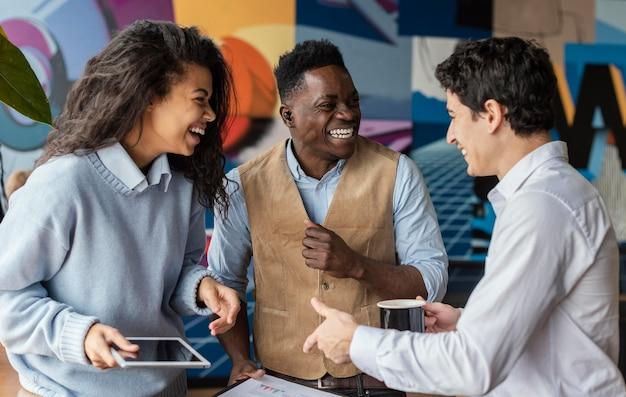 Compañeros de trabajo sonrientes en la oficina conversando