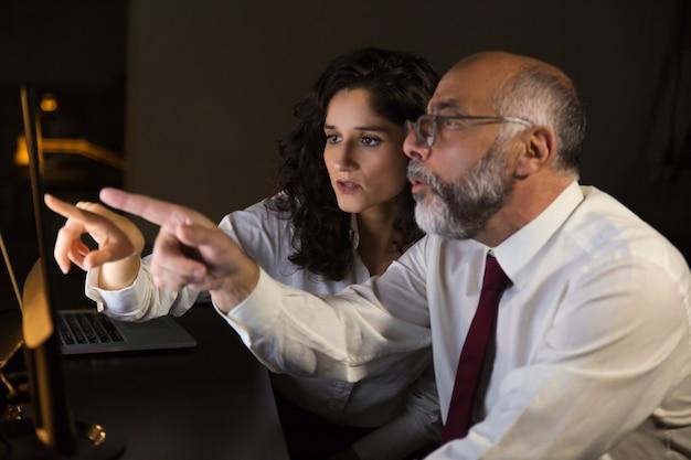 Compañeros de trabajo sorprendidos apuntando al monitor de la computadora