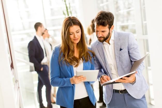 Compañeros de trabajo con tableta en la oficina moderna y discutir