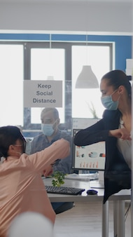 Compañeros de trabajo tocándose el codo para evitar la infección con el coronavirus equipo de negocios con máscara médica ...