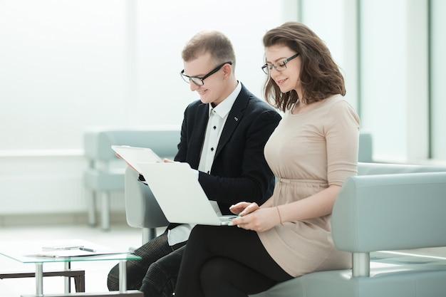 Compañeros de trabajo usan gadgets sentados en el pasillo de la oficina