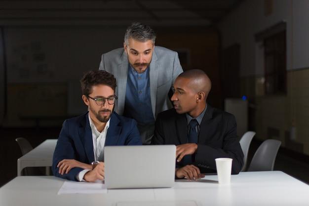 Compañeros de trabajo usando laptop en la oscura oficina