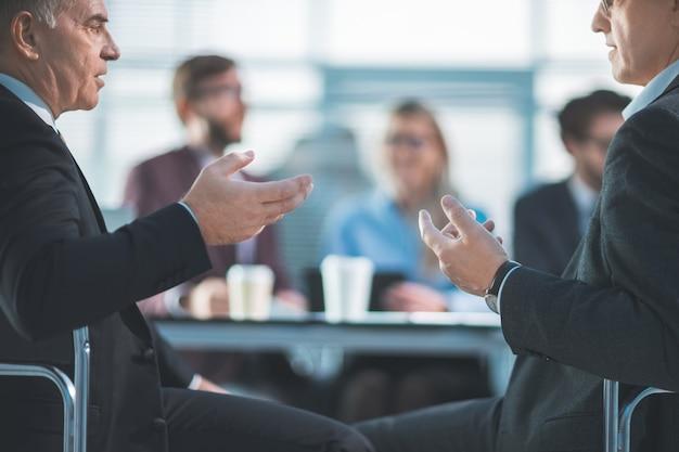 Compañeros de trabajo de vista trasera discuten sentado en la mesa de la oficina