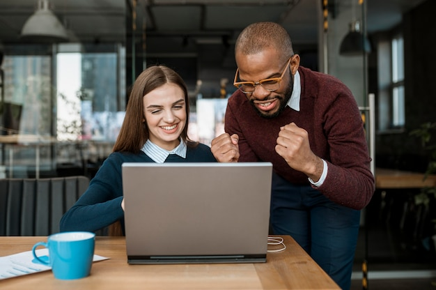 Compañeros victoriosos que descubren buenas noticias en una reunión