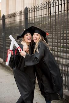Compañeros de la vista frontal abrazando en la graduación