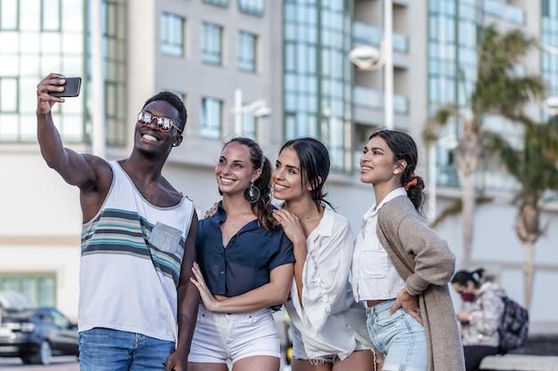 Compañía de alegres amigos diversos tomando selfie en ciudad