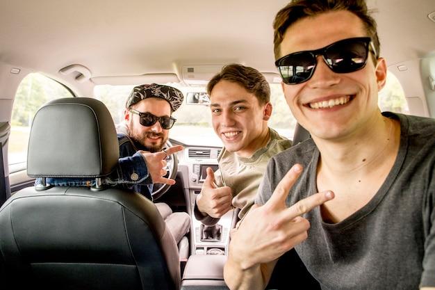 Compañia de alegres amigos sentados en carro en viaje.