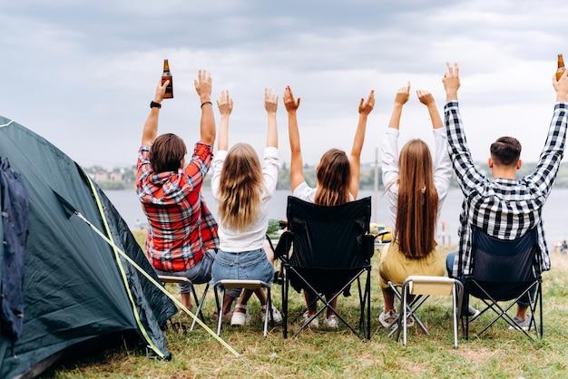 Una compañía de amigos almuerza en el campamento. ellos levantan las manos. - vista trasera