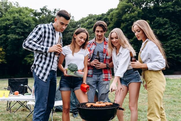 Una compañía de amigos con bebidas y comida cocinando en la barbacoa en el campamento. - imagen