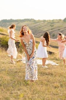 La compañía de amigos felices divirtiéndose y bailando afuera en un picnic en las colinas.