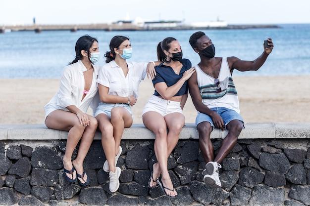 Compañía de amigos multiétnicos tomando selfie en terraplén