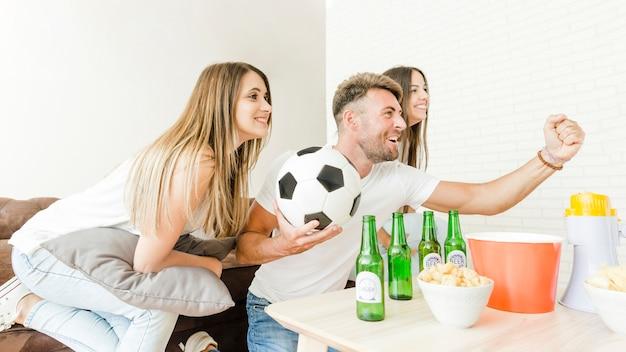 Compañía de amigos que se regocijan viendo fútbol en televisión