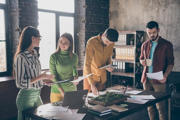 Compañía de cuatro empleados agradables, atractivos, inteligentes, inteligentes, alegres, amigables, preparando la estrategia del plan
