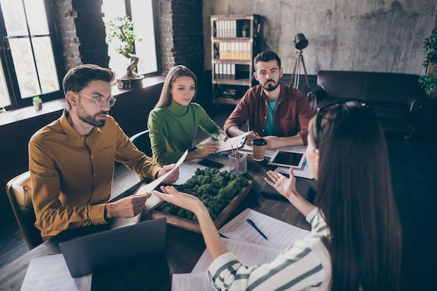 Compañía de cuatro expertos gerentes ejecutivos de empresarios calificados enfocados atractivos agradables sentados alrededor de la mesa discutiendo