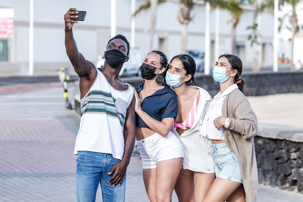 Compañía de diversos amigos en máscaras tomando selfie en la calle
