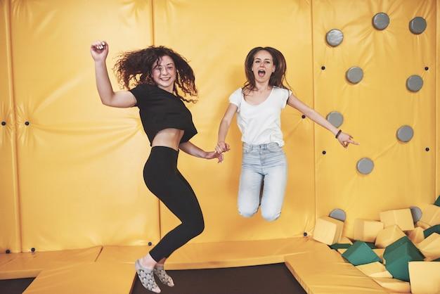 La compañía es una mujer joven que se divierte con bloques suaves en un parque infantil en un centro de trampolines.