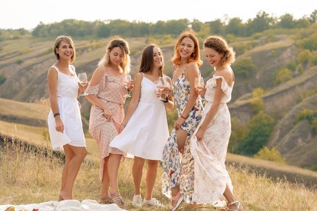 La compañía de hermosas amigas se divierte y disfruta de un picnic de verano, baila y bebe alcohol. concepto de personas