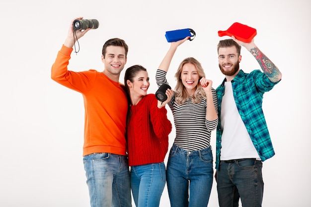 Compañía joven inconformista de amigos divirtiéndose juntos sonriendo escuchando música en altavoces inalámbricos, bailando riendo