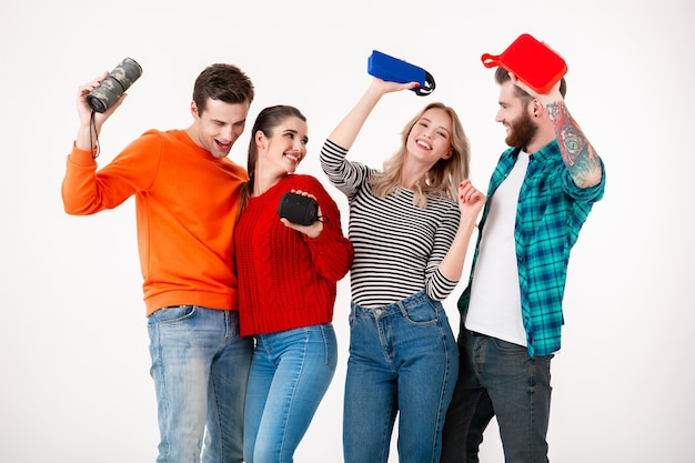 Compañía joven inconformista de amigos divirtiéndose juntos sonriendo escuchando música en altavoces inalámbricos