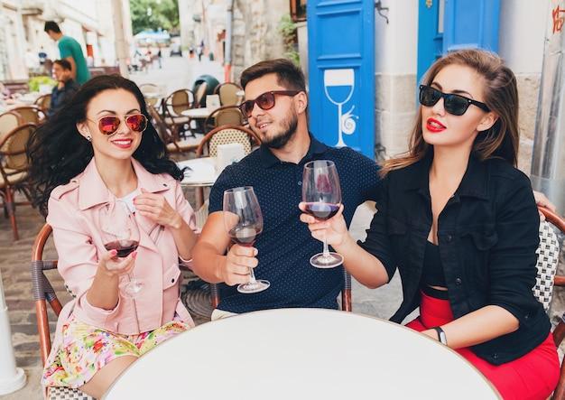 Compañía joven inconformista de amigos sentados en el café de la calle de la ciudad