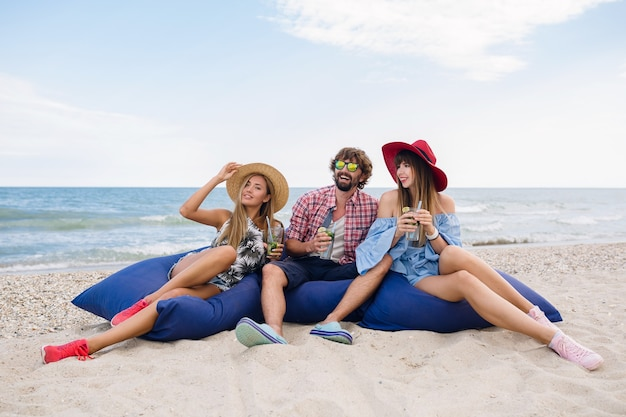 Compañía joven inconformista de amigos de vacaciones en el café de la playa, bebiendo un cóctel mojito, feliz positivo, estilo veraniego, sonriendo feliz, dos mujeres y un hombre divirtiéndose juntos, hablando, coqueteando, romance, tres