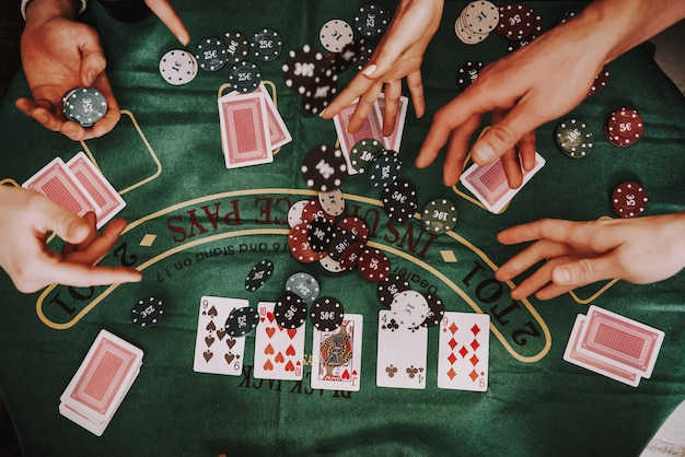Compañía joven jugando holdem poker en una fiesta.