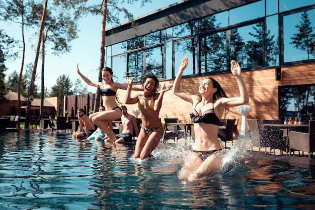 Una compañía de jóvenes descansa junto a la piscina.