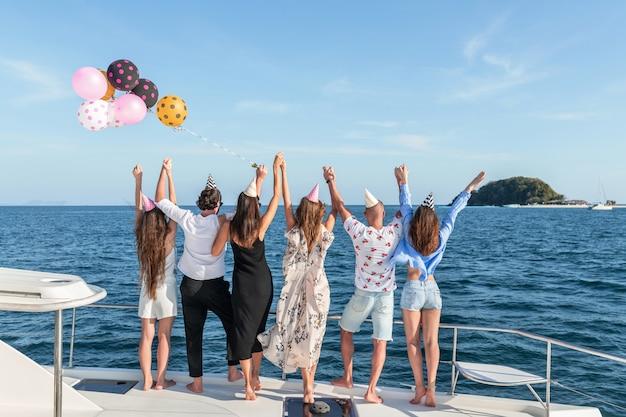 Una compañía de jóvenes hermosos con gorros de vacaciones está parada en el borde del yate, levantando sus manos hacia la cima.
