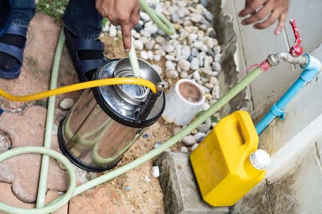 La compañía de personal de termitas de tailandia asiática está rociando el líquido químico destructor en el nido de hormigas blancas en la madera alrededor de la casa humana.