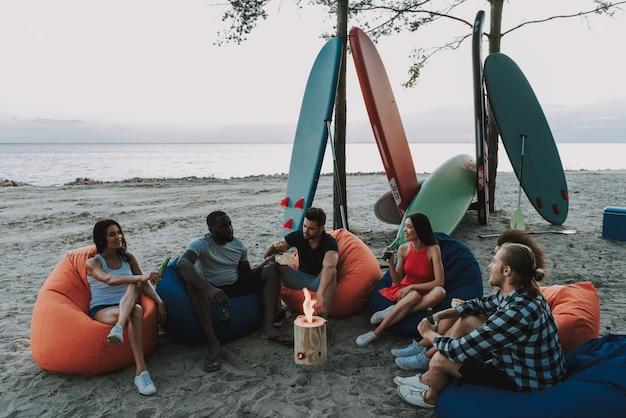 Compañía de surfistas comiendo bocadillos en la playa.