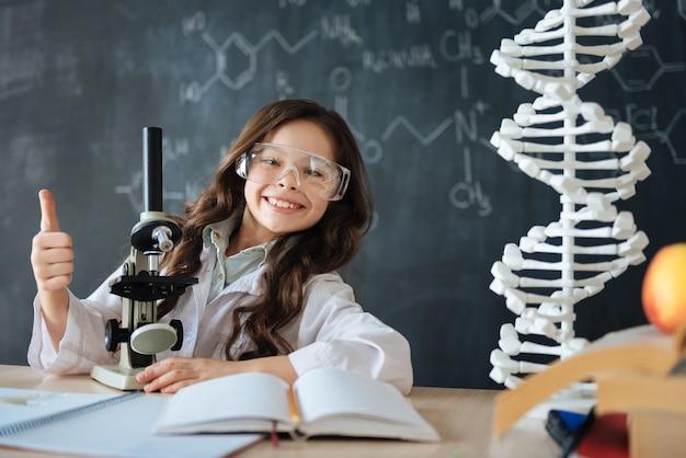 Compartiendo emociones positivas. sonriente niño satisfecho encantado de pie en el laboratorio y disfrutando de la clase de biología mientras participa en el proyecto de ciencias y usa el microscopio