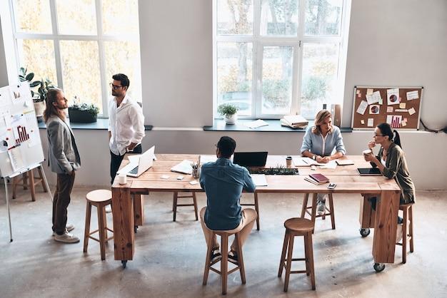 Compartiendo ideas interesantes. vista superior de los jóvenes modernos que se comunican mientras trabajan juntos en la sala de juntas