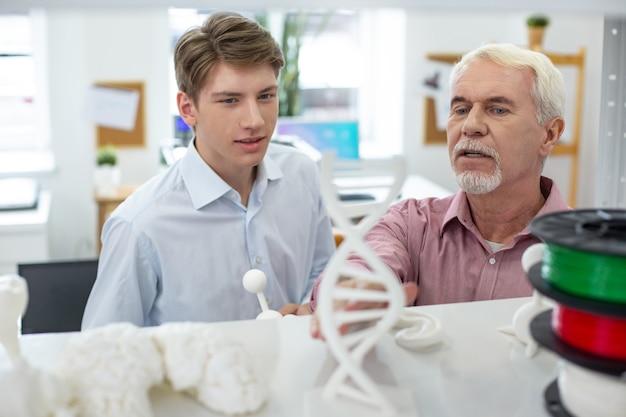 Compartiendo información. encantador hombre mayor discutiendo modelos 3d con su joven pasante mientras está de pie frente a un estante con la colección de modelos impresos
