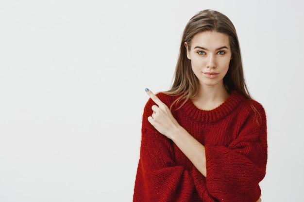 Compartiendo lugar secreto con nosotros. segura emprendedora atractiva con suéter rojo suelto, sonriendo con expresión intrigada y segura, apuntando a la esquina superior izquierda