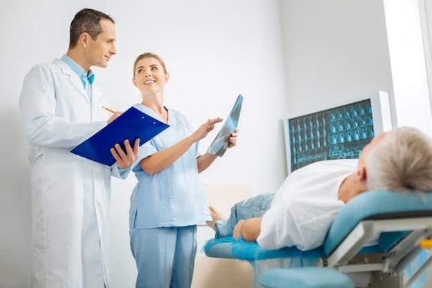 Compartiendo opiniones. doctores felices, positivos y encantados parados juntos y hablando mientras comparten sus opiniones sobre el diagnóstico