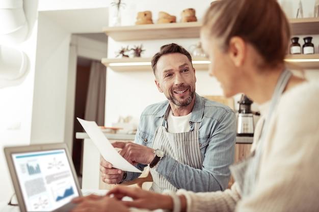 Compartiendo pensamientos. hombre guapo sonriendo a su esposa apuntando en una hoja de papel mientras trabajan juntos.