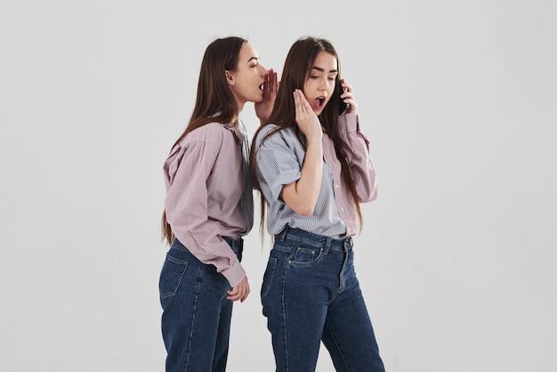 Compartiendo con secretos. dos hermanas gemelas de pie y posando