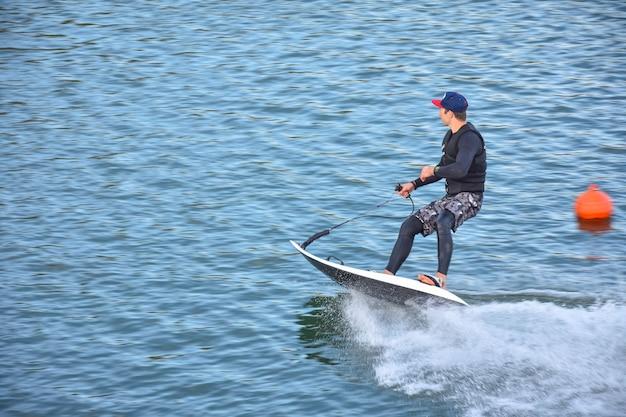 Competidor de motosurf tomando una curva a gran velocidad haciendo mucho spray. jet surf en el agua, hombre montado en una tabla de surf jet. surfista en movimiento, deporte de verano